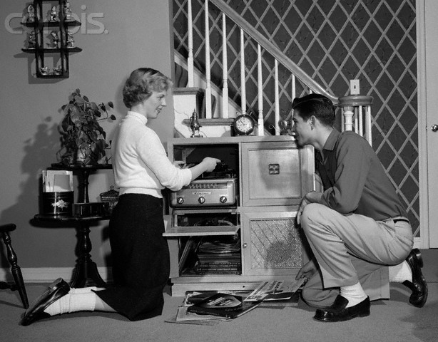 1950s Teenage Couple Playing Hi-Fi Records On Console Phonograph In Living Room